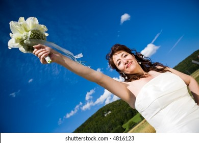 Fancy Perspective. Bride holds her bridal bouquet on outstretched arm. Deepblue sky as background. Sunny weather. Adult bride.