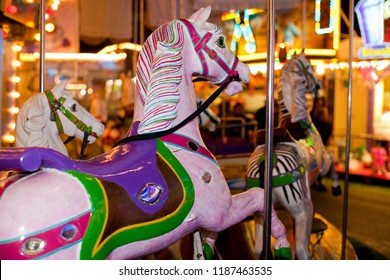 fancy pink horse with violet and green seat on a vintage childrens' carousel at a fairground at night