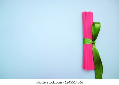 fancy pink spaghetti tied with a green ribbon on a blue background copy space, non-food