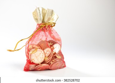A fancy red bag full of UAE dirham coins on white background. UAE dirham coins in a red pouch.