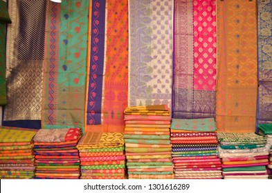 Fancy sarees / unstitched suits hanging and folded on display in a Swadeshi khadi handloom exhibition at Dilli Haat, New Delhi, India International Trade Fair (IITF)