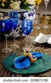 Fancy table setting with sous plat, blue glasses and a flower vase at the back