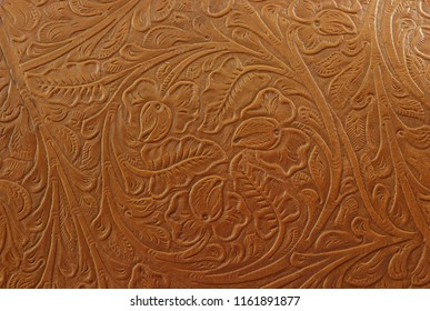 A fancy tan brown light colored background made of imprinted leather, with flowers and floral and cowboy western designs.