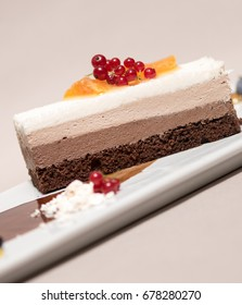 Fancy triple mousse chocolate dessert, placed on a white plate, decorated with forest fruits and chocolate sauce, white plate, light brown background