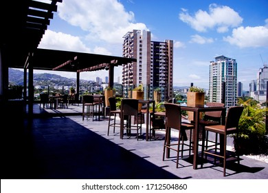 The a fancy view of a bar and restaurant located at the roof deck of a hotel!