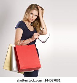 Fancy young woman model with shopping bags posing in studio. Pretty Caucasian blonde female holding sunglasses.