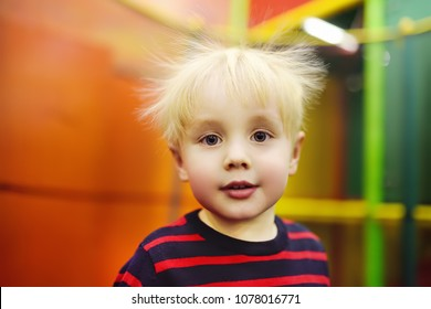 Fanny hairstyle of little boy after activity on trampoline. Child playing on indoor playground. Kid jumping on trampoline