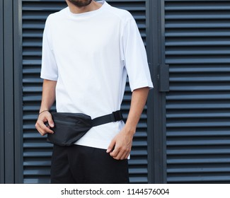 Fanny pack, bum bag. Youth street fashion for men. A man in a summer day in the street in a fashionable outfit. White trendy T-shirt and bag. Part of the body.