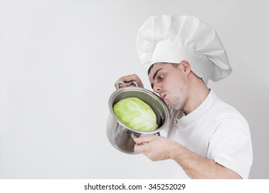 fanny young adult man in white uniform holding pot inserted in green head of cabbage against gray texture background Idea of raw food eating Empty copy space for inscription