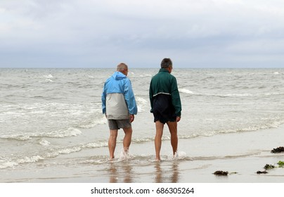 FANOE, DENMARK - JULY 23, 2017: Two middle-aged men walking on the beach. Cold danish summer on shore of the North Sea.