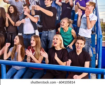 Fans cheering in stadium. Group people wait your favorite team and worry on tribunes. Youth support your favorite team. Young men and women are dressed in light clothing and jeans.