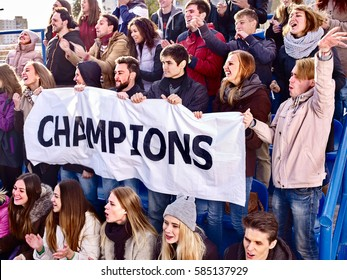 Fans cheering in stadium holding champion banner and singing on tribunes. Large group young people together support your favorite team. Cold weather outdoor.