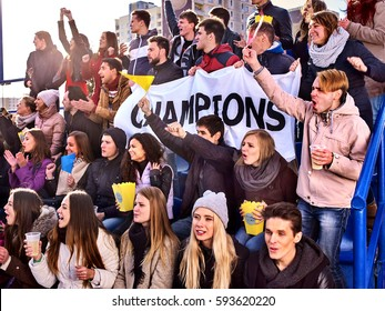 Fans cheering in stadium holding champion banner and singing on tribunes. Large group people together support your favorite team. People holding banner with Champion banner happily eating popcorn.