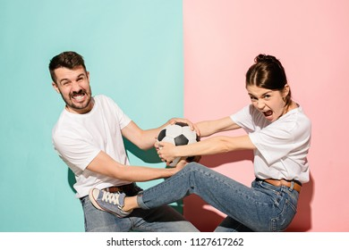 Fans of different teams. The unhappy and angry fans with ball on colored blue and pink background. The young man and woman are enemies. Fan, support concept. Human emotions concept.