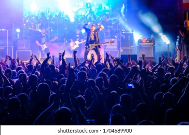 Fans at live rock music concert cheering musicians on stage, back view - Shutterstock ID 1704589900