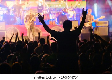 Fans at live rock music concert cheering musicians on stage, back view