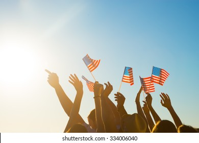 Fans on the concert of your favorite pop stars. Young people waving American flags. Fans at the match with his arms raised. Pride in their country.