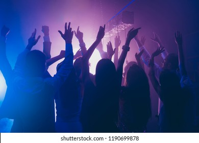 Fans rest, relax, chill waving raised hands cheering in night club having fun, carefree, careless mood