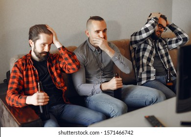 Fans sitting on the couch in the living room. Guys drinking a beer