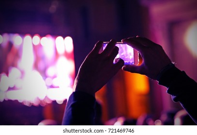 fans take photos and record videos with modern smartphones during live concert of a rock band on stage