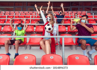 Fans watching football match under social distancing measures in stadium wearing masks