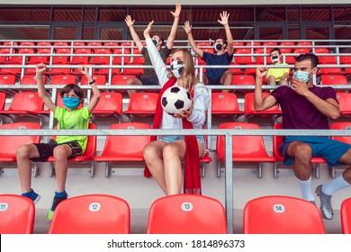 Fans, die Fußballspiele im Stadion mit Masken ansehen und dabei soziale Distanzmaßnahmen in Anspruch nehmen