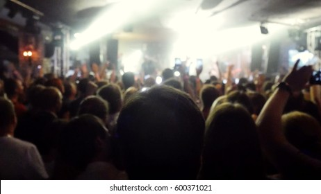 Fans waving their hands and hold the phone with digital displays the crowd at concert.