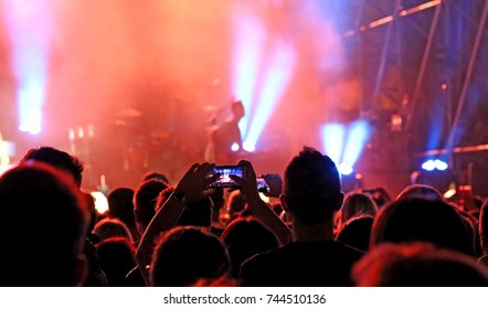 fans who take pictures and record videos with modern smartphones during the live concert of a rock band