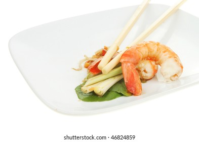 Fantail prawns with salad garnish and chopsticks on a white plate