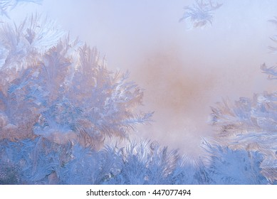Fantastic abstract winter background (frost pattern on a window glass at the dawn), winter morning