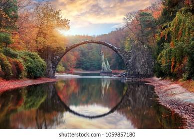 Fantastic Autumn Landscape. Amazing sunset With colorful sky in Azalea and Rhododendron Park Kromlau .Rakotz Bridge, Rakotzbrucke Devil's Bridge in Kromlau, Saxony, Germany. Creative Artistic image.