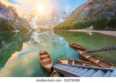 Fantastic autumn landscape with boats on the lake with sunrise on Fanes-Sennes-Braies natural park. Dolomites, Alps, South Tyrol, Italy, Europe. (holiday, inner peace, harmony, honeymoon - concept)