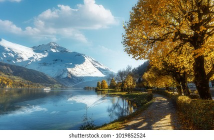 Fantastic Autumn Landscape. Wonderful Alpine Highland with majic lake. Ice peak on the Background. reflected in azure clear water. Creative colage. Impressively Beautiful View.