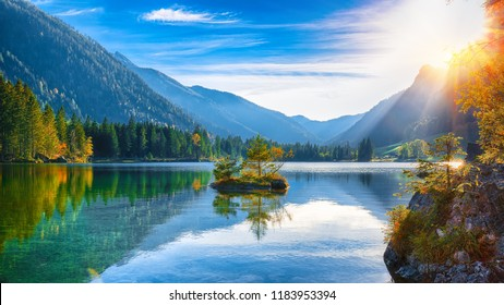 Fantastic autumn sunset of Hintersee lake. Beautiful scene of trees on a rock island. Location: resort Ramsau, National park Berchtesgadener Land, Upper Bavaria, Germany Alps, Europe