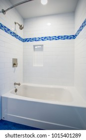 Fantastic bathroom with a drop-in tub and shower combo framed by a white subway tiled backsplash fitted with a niche flanked by blue mosaic border tiles.