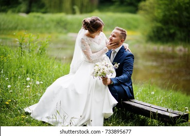 Fantastic bride sitting on a groom's lap in the meadow next to the lake on a wedding day.