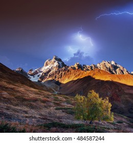 Fantastic collage. Beautiful lightning over the snow-capped mountain peaks. Autumn landscape. Main Caucasian Ridge. Georgia. Europe. Art photography