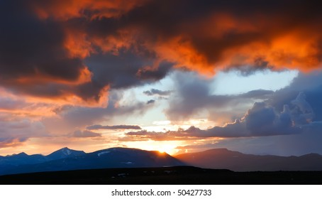 Fantastic colorful red sunset. The sun is setting beyond the mountain ridge and fire red flame on the sky
