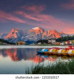 Fantastic Colorful sunset over calm lake in Dolomites Alps. Sunrise over Misurina Lake. Great rocks over the lake Misurina in National Park Tre Cime di Lavaredo. Awesome Nature Landscape.