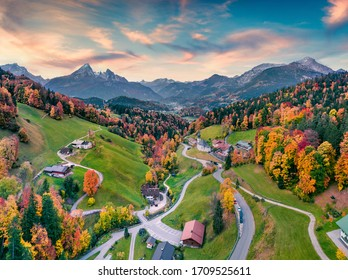 Fantastic evening view from flying drone of Maria Gern church with Hochkalter peak on background. Incredible autumn scene of Bavarian Alps. Colorful landscape of Germany countryside.