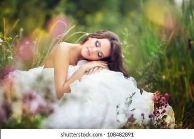 fantastic fairy bride in a wedding dress sits at green grass among flowers with closed eyes.