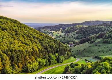 Fantastic Franconian Spring Landscape in Germany. Beautiful Road in the forest hills of northern Bavaria at sunset. Fresh Deciduous Forest Scenery