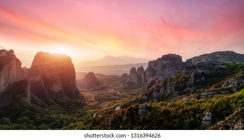 Fantastic Landscape with monasteries and rock formations in Meteora during sunset, Greece. Mysterious Sunny Morning with colorful sky. Awesome Nature Landscape. Popular travel locations.