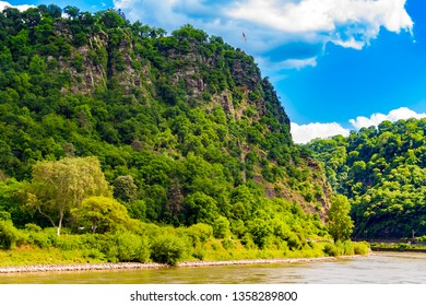 Fantastic landscape view of the steep Lorelei (Loreley in German) Rock on the riverbank of the River Rhine in the Rhine Gorge at Sankt Goarshausen in Germany. The top is marked by two flags.
