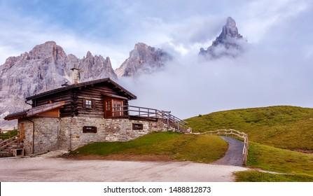 Fantastic misty landscape of Dolomites mountains. Amazing Alpine scenery Baita Segantini mountain refuge with Cimon della Pala peak. Beautiful nature Scenery. Dolomites Alps. Italy. Europe