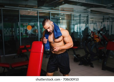 A fantastic muscular bodybuilder relaxing after a hard training with a blue towel and listening to music. A shirtless, hot male athlete with headphones and a smart phone on a blurred gym background.