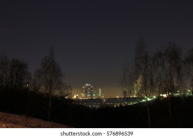Fantastic night city with skyscrapers far behind
