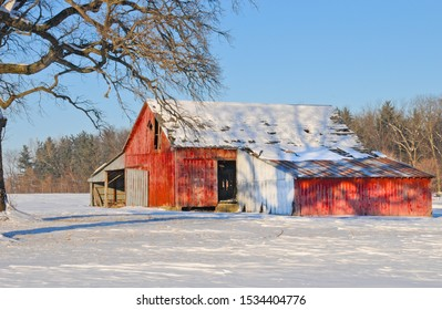 Fantastic old red barn sitting under blue skies with a blanket of white snow in Central Illinois