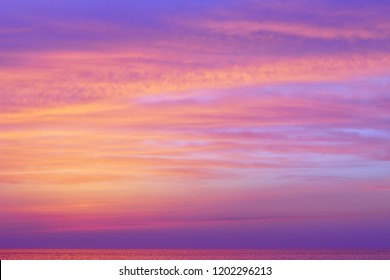 Fantastic pink clouds over the sea after sunset. Soft focus
