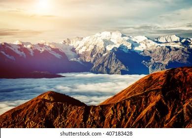 Fantastic range in mist at the foot Ushba. Dramatic foggy scene. Location place Svaneti, Mestia, Georgia, Europe. High Caucasus ridge. Beauty world. Retro and vintage style. Instagram toning effect